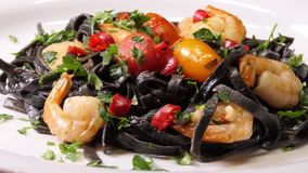 Black squid ink Fettuccine pasta with prawns or shrimps cherry tomatoes, parsley, chili in wine and butter sauce. Spin shot. stock video