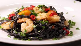 Black squid ink Fettuccine pasta with prawns or shrimps cherry tomatoes, parsley, chili in wine and butter sauce. Zoom in shot stock footage
