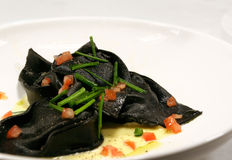 Black Squid Ink Ravioli. With tomato and spring onion garnish Stock Images