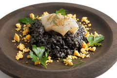 Black squid ink risotto with grilled calamary. Black risotto dyed with squid ink and grilled calamary on round wooden plate Royalty Free Stock Photography
