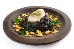 Black squid ink risotto with lightly seared calamar. Black squid ink risotto with fried calamari in wooden plate, isolated on white Stock Photography
