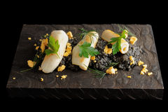 Black squid ink risotto with lightly seared calamary. Black isotto with squid ink and seared calamary on wooden board, isolated on black Royalty Free Stock Photography