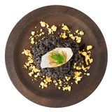 Black squid ink risotto with seared calamar on round wooden plat Royalty Free Stock Photography