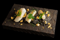 Black squid ink risotto with seared calamary. Black squid ink risotto with lightly seared calamary on wooden board, isolated on black Stock Images