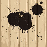 Black stains on beige wood background Stock Images