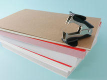 Black staple remover with books (#1). Black staple remover with brown notebook and books on bright blue background. (#1 Royalty Free Stock Photo
