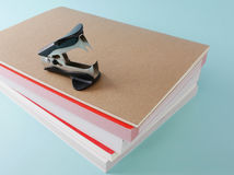 Black staple remover with books (#2). Black staple remover with brown notebook and books on bright blue background. (#2 Stock Images