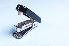 Black stapler  on white background. School and office supplies on the desktop. Copy space. The concept of school and stock photography