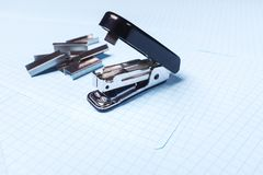 Black stapler and staples  on white background. School and office supplies on the table. Copy space. The concept of school stock photo