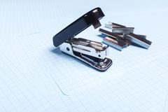 Black stapler and staples isolated on white background. School and office supplies on the table. Copy space. The concept of school stock images