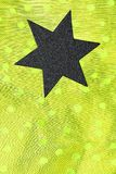 Black star on yellow fabric. A black six-pointed star on an yellow dotted background Royalty Free Stock Photos
