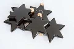 Black Stars. Black star-shaped Christmas tree decorations isolated in the studio Stock Image