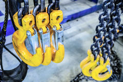Black steel chain and yellow cargo hooks. Royalty Free Stock Images