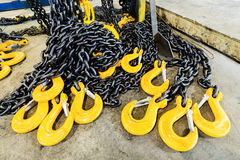 Black steel chain and yellow cargo hooks. Royalty Free Stock Image