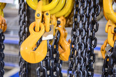 Black steel chain and yellow cargo hooks. Stock Photography