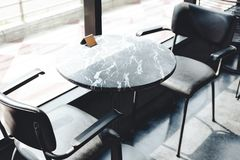 Black Steel Chairs And Round Black Granite Top Table Near Glass Window With Direct Sunlight Stock Image