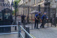 Black steel closed gates protecting the entrace to Downing Street, with armed police. Downing Street, London, UK - June 8, 2018: Armed police protecting the stock images