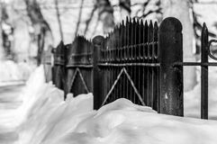 Black steel fence. Winter, snowdrifts, trees, cityscape, Russia Stock Photography