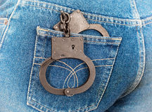 Black steel handcuffs in jeans pocket Stock Photos