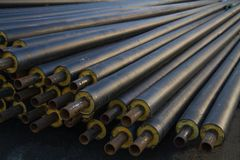 Black steel pipe with heat insulation on the construction site in a plastic tube wrapper lying on the pavement a bunch of horizont Stock Images
