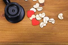 Black Stethoscope and Heart-Shaped Wooden Pieces Stock Images