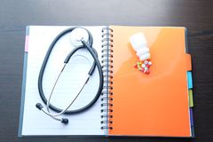 Black stethoscope and medicin on book. Health awareness concept. Black stethoscope and medicin on book. Health awareness concept Stock Photography