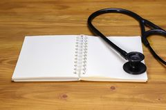 a black stethoscope and a white spiral notebook Stock Photography