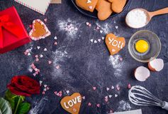 Black stone background with frame of homemade cookies in shape of heart, flower, food ingredients and decor. Prepearing gift for l. Over on Valentine`s day. Love Stock Photo
