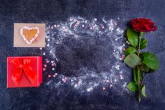 Black stone background with frame of powdered sugar and sugar candy hearts decor with roze and gift box. preparation gift for love. R on Valentine`s day Stock Photo