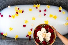 Black stone bath with white water and tropical flowers, roses petals. Luxury spa, organic skin treatment concept. Background stock photo