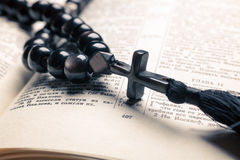 Black stone christianity beads with cross on bible. With Cyrillic letters on wooden desk stock image