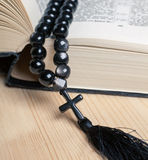 Black stone christianity beads with cross on bible Royalty Free Stock Photography