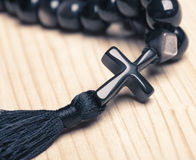 Black stone christianity beads with cross on wooden desk Royalty Free Stock Image