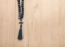 Black stone christianity beads with cross on wooden desk Stock Photo