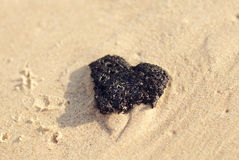 Black stone heart. On the sand Royalty Free Stock Photo