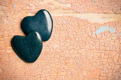 Black stone hearts on old cracked background Stock Photos