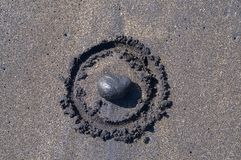 Black stone laid in a circle drawn on black sand royalty free stock photo
