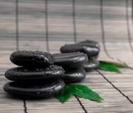 Black stone with leaf. massage Stock Images