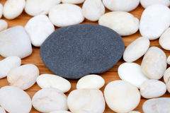 A black stone and many small white stones Royalty Free Stock Photo