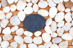 A black stone and many small white stones Royalty Free Stock Images