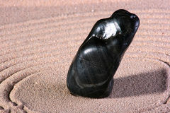 Black stone is on sand Stock Photography
