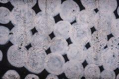 Black stone wall drawing, white circles, texture. Rough Stock Image