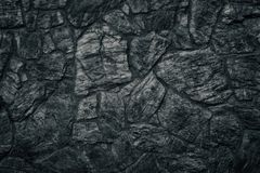 Black stone wall texture as sinister Gothic background. Black stone wall texture. Dark sinister Gothic background stock photo