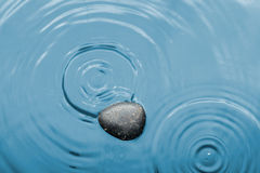 Black stone in the water under the rain Royalty Free Stock Photo
