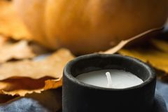 Black Stone White Candle Orange Pumpkin Dry Colorful Autumn Leaves on Blue Linen Cloth. Cozy Contemplative Atmosphere.Thanksgiving. Black Stone White Candle Stock Images
