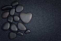 Black stones with black zen heart shaped rock Royalty Free Stock Photos
