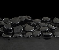 Black stones on calm water Royalty Free Stock Photography