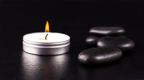 Black stones and a candle on black  background Stock Image