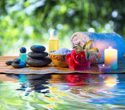 Stones, candle camellia oil salt towel on water. Black stones, candles, red camellia, oil, salt, towel on water ripple stock image