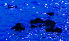 Black stones in deep blue water Royalty Free Stock Image